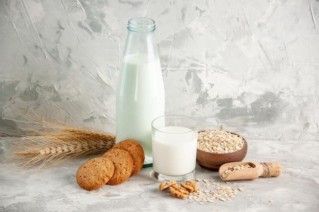 Vista dall'alto della bottiglia di vetro e della tazza piena di latte su vassoio di legno e biscotti con cucchiaio di avena in vaso marrone su tavolo bianco su sfondo di ghiaccio