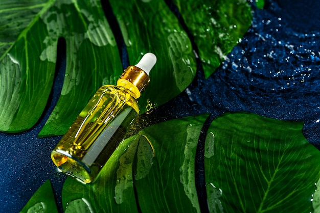 Top view glass bottle with white pipette lies on water and green leaves on classic blue background , eco natural cosmetic concept