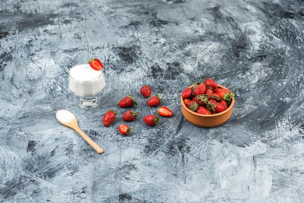 Top view a glass bowl of yogurt on wicker placemat with wooden spoon and strawberries on dark blue marble and white wooden board surface. vertical