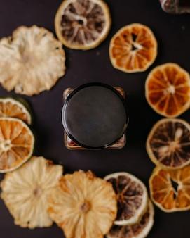 Una lattina di vetro vista dall'alto insieme ad anelli di frutta secca sulla scrivania scura
