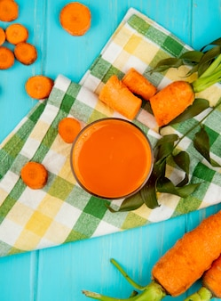 Top view of glass of carrot juice with cut and sliced carrots on cloth decorated with leaves on blue background