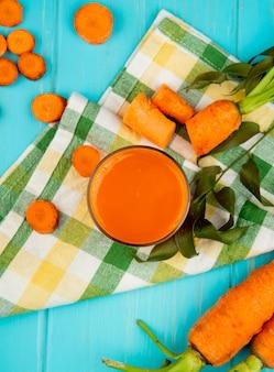 Vista superiore di vetro del succo di carota con le carote tagliate ed affettate sul panno decorato con le foglie su fondo blu