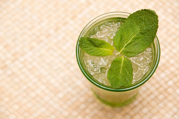 Top view of a glass of iced tea with mint leaves on the table