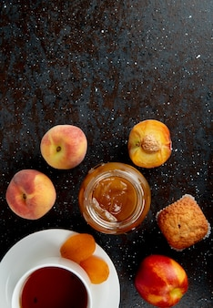 Top view of glass jar of peach jam with peaches cupcakes and cup of tea on black and brown surface with copy space