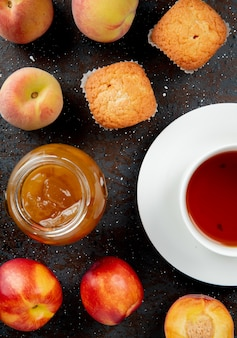 Top view of glass jar of peach jam with peaches cupcakes and cup of tea on black and brown surface