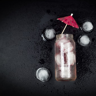 Top view glass jar with red cocktail and ice, decorated with umbrella