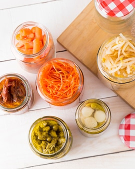 Top view of glass jars with baby carrots and other vegetables