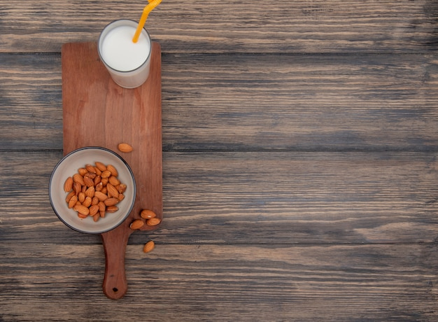 Top view of glass of milk with drinking tube and bowl of almonds on cutting board on wooden background with copy space