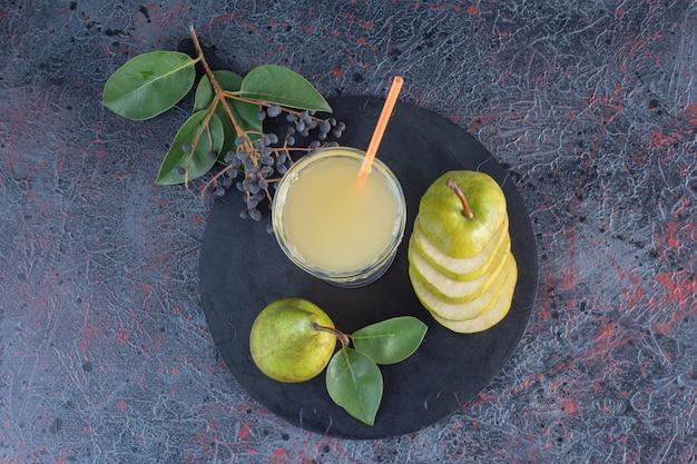上面図。木の板に緑色のスライスした梨と梨ジュースのガラス
