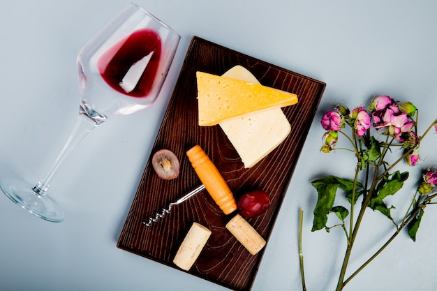 Top view of glass of red wine with flowers and grape cheddar and parmesan cheese corks and corkscrew on cutting board on white table