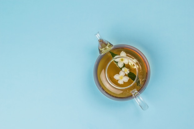 Top view of a glass teapot with jasmine tea on a blue background. an invigorating drink that is good for your health.