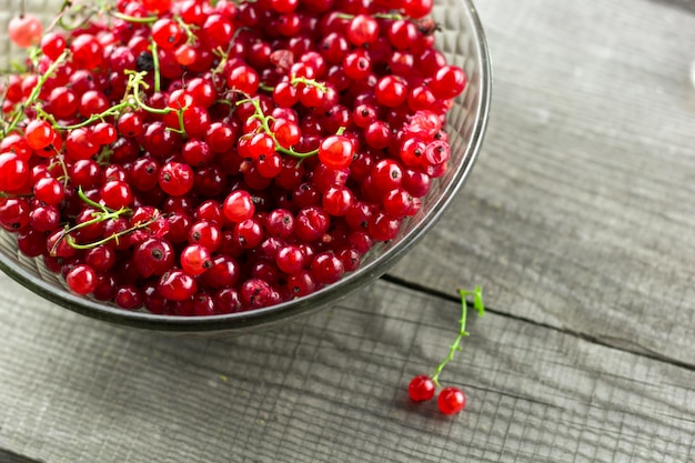 Top view glass vintage bowl full of red ripe currant berries on a wooden table
