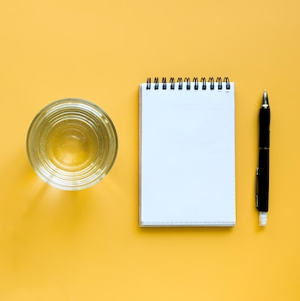 Top view of glass of water with notebook and pen
