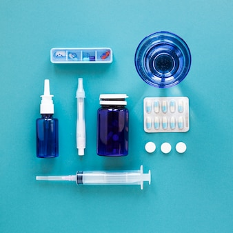 Top view glass of water with pills and needle