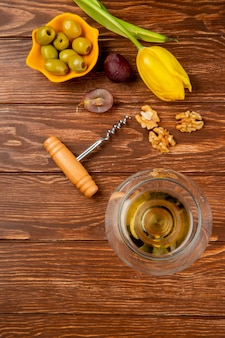 Top view of glass of white wine with olive walnut grape corkscrew and flower on wooden table