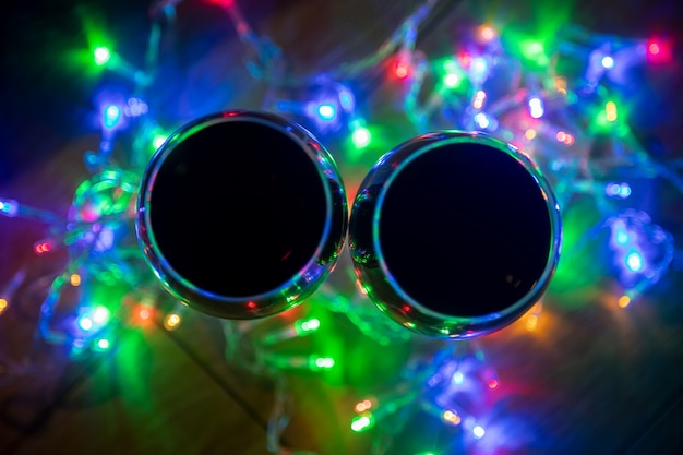 Top view of glass wine glasses in shining christmas garland on dark background