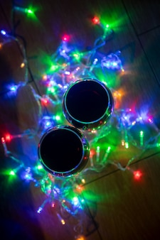 Top view of glass wine glasses in shining christmas garland on dark background....