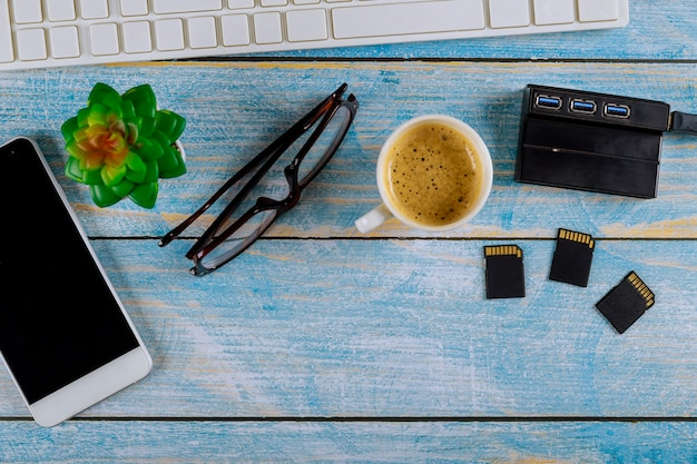 Top view glasses and coffee, laptop with external hard drive disk, sd card on photographers desktop wooden table