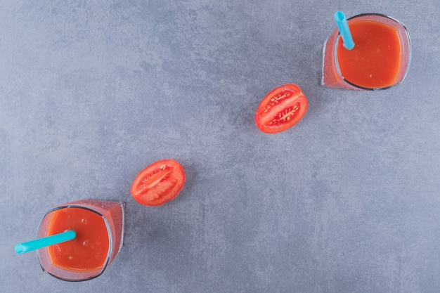 Top view of glasses of fresh tomato juice and tomatoes on a grey background.