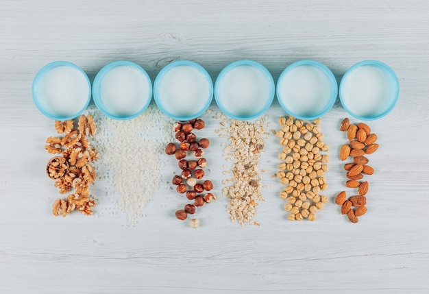 Top view glasses of milk with almonds. hazelnuts, oats and several nuts on white wooden background. horizontal