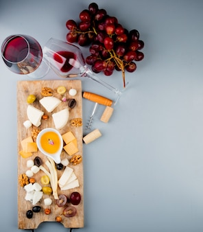 Top view of glasses of red wine with cheese grape olive nuts butter on cutting board and corkscrew on white with copy space