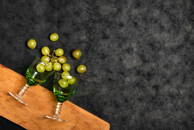Top view glasses with grapes on slate background