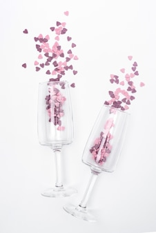 Top view of glasses with heart-shaped confetti