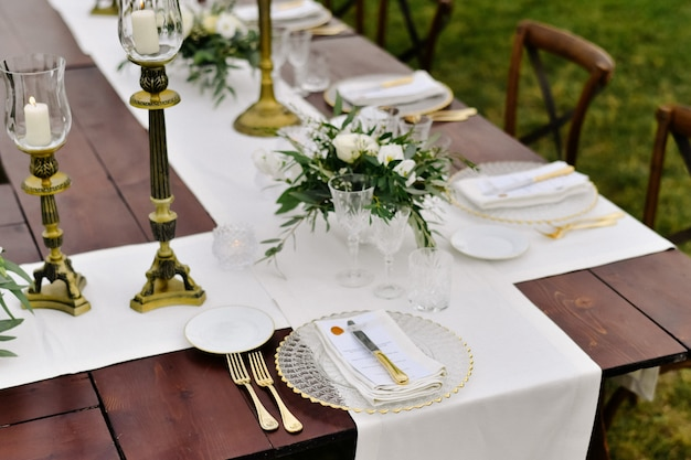Top view of glassware and cutlery on the wooden table outdoors, with white eustomas and ruscus bouquets