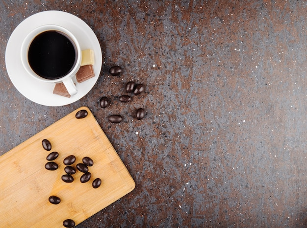 Top view of glazed chocolate nut candy scattered on a wooden board and a cup of coffee on black background with copy space