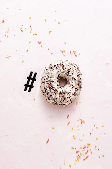 Top view of glazed doughnut with sprinkles and hashtag symbol