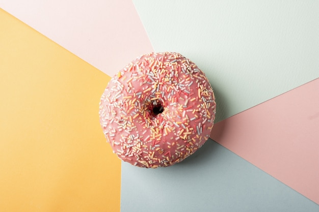 Top view of glazed doughnut with sprinkles and multicolored background