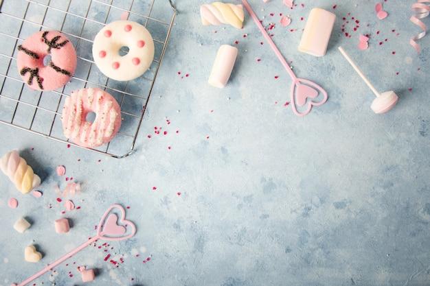 Vista dall'alto di ciambelle glassate con assortimento di caramelle e marshmallow