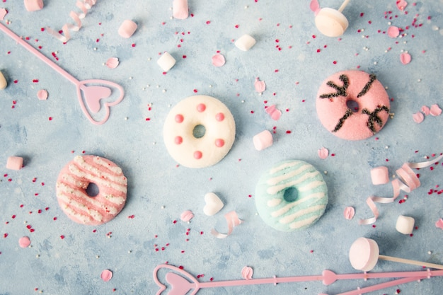 Top view of glazed doughnuts with assortment of candy