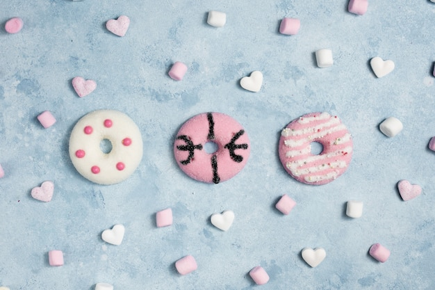 Top view of glazed doughnuts with marshmallow and hearts