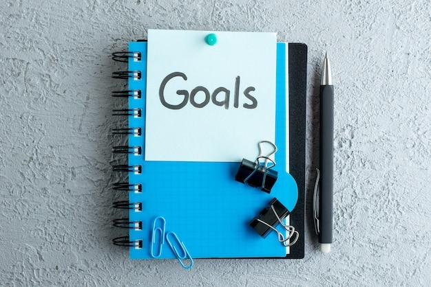 白い表面の色の学校の仕事のコピーブック大学のオフィスにメモ帳とペンでメモを書いたトップビューの目標