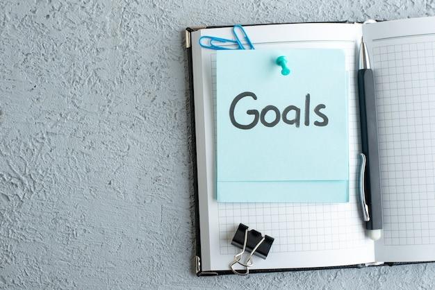 Vista dall'alto obiettivi nota scritta con blocco note e penna su sfondo bianco ufficio scuola lavoro quaderno colore college