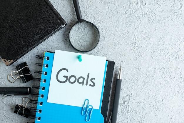 Vista dall'alto obiettivi nota scritta con blocco note e penna sullo sfondo bianco ufficio colore scuola college lavoro quaderno aziendale