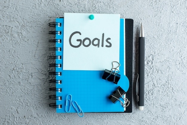 Top view goals written note with notepad and pen on white surface color school job business copybook college office