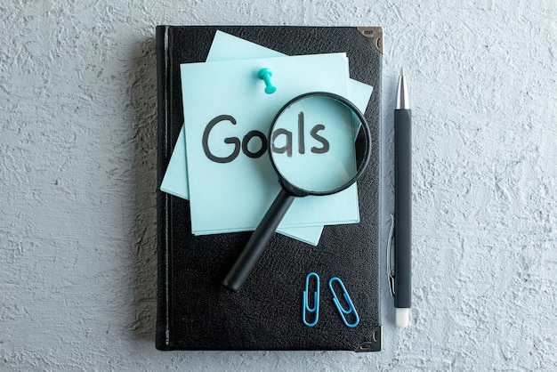 Top view goals written note with notepad and pen on white surface job office school copybook color college business