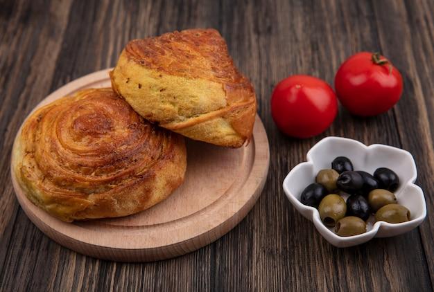 Vista dall'alto di gogals su una tavola da cucina in legno con olive su una ciotola e pomodori freschi isolati su uno sfondo di legno