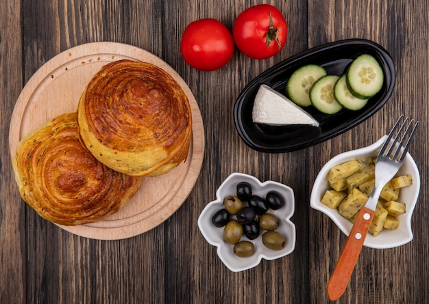 Top view of gogals on a wooden kitchen board with olives on a bowl with white cheese and cucumber slices on a black bowl on a wooden background