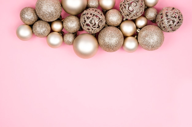 Top view gold balls christmas decoration composition on a pink background.