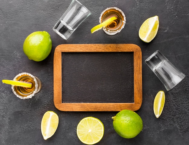 Top view gold tequila shots and lime with blank blackboard
