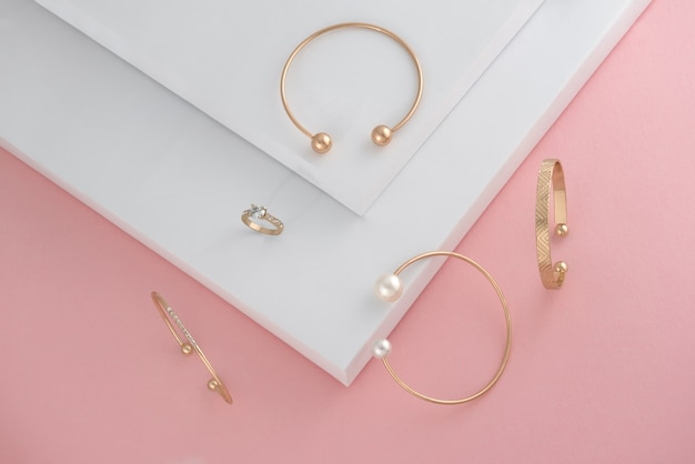 Top view of golden accessories on pink and white background with copy paste