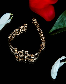 Top view of golden bracelet with diamonds on black wall