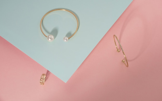 Top view of golden bracelets and ring on pink and blue background with copy space