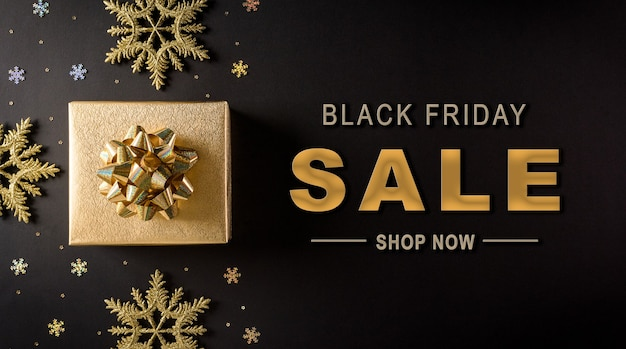 Top view of golden christmas boxes and snowflake on black background with black friday sale text