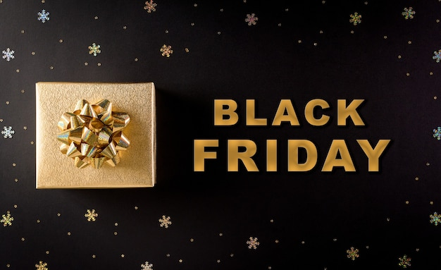 Top view of golden christmas gift boxes on black background with black friday text