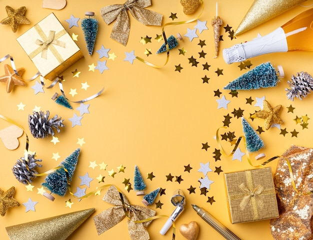 Top view of golden christmas and new year decorations with confetti and gift boxes flat lay