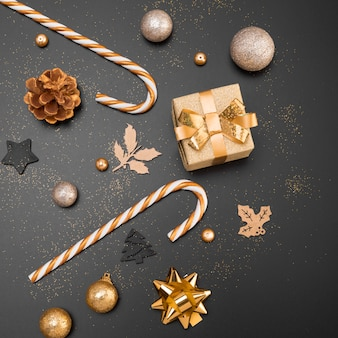 Top view of golden christmas ornaments with present and candy canes